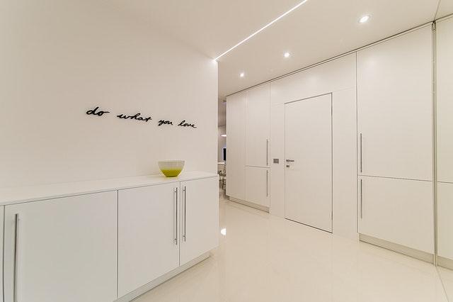Minimalisticky pojatá chodba s bílými vestavěnými skříněmi