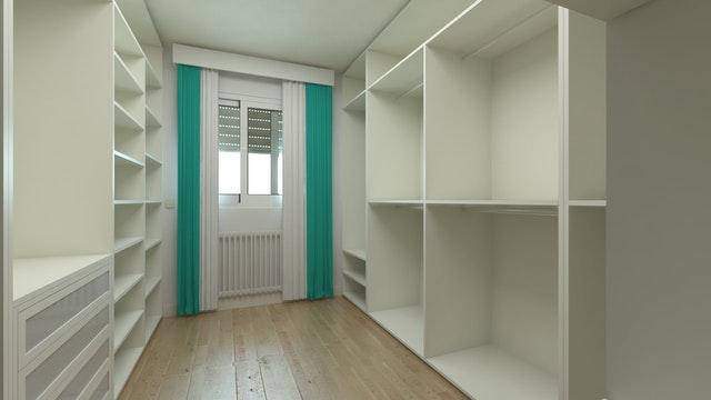 Interiér šatny vybavený bílými regály a zásuvkami